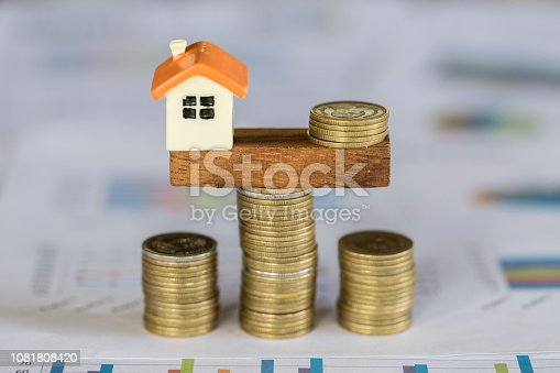 1048402108istockphoto Model house and money coins balancing on a seesaw, Property real estate investment ideas, Concept of risk house mortgage, loan financial management. 1081808420