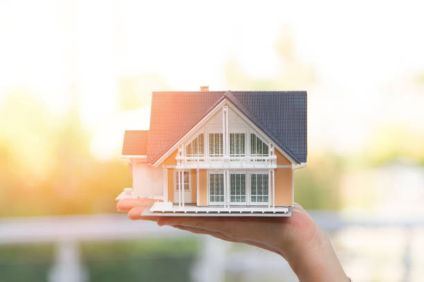 Model house in woman hand Real estate insurance concept - young woman hands saving miniature house home insurance stock pictures, royalty-free photos & images