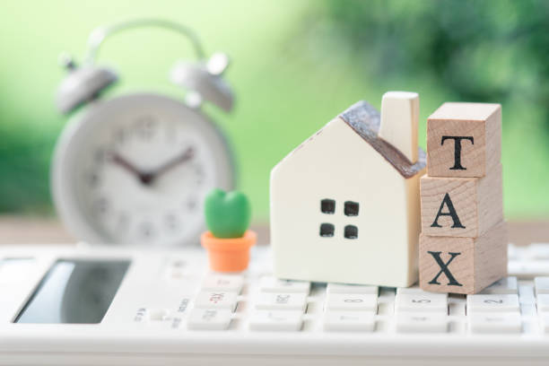 A model house model is placed on wood word TAX . as background property real estate concept with copy space for your text or design. A model house model is placed on wood word TAX . as background property real estate concept with copy space for your text or design. grounds stock pictures, royalty-free photos & images