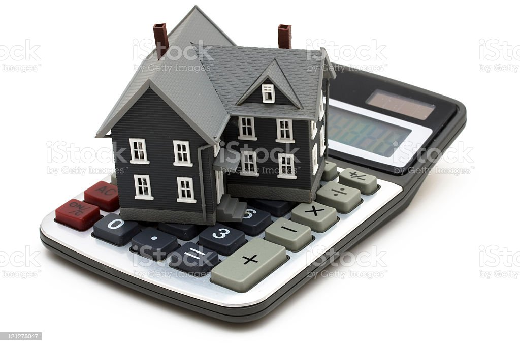 Model house on top of calculator on white background stock photo