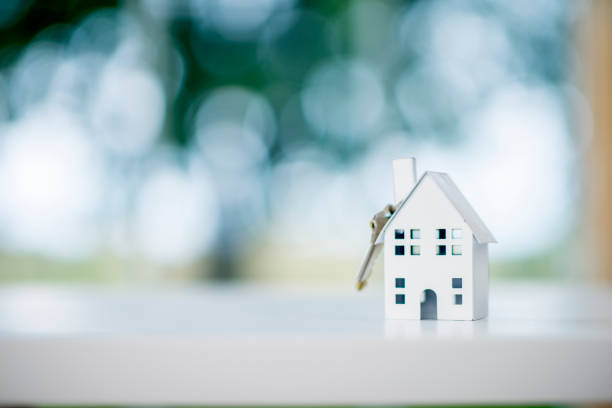 Model House With Key A miniature model house is sitting on a desk. A house key is dangling from the roof. The scene symbolizes purchasing a new house. mortgage loan stock pictures, royalty-free photos & images