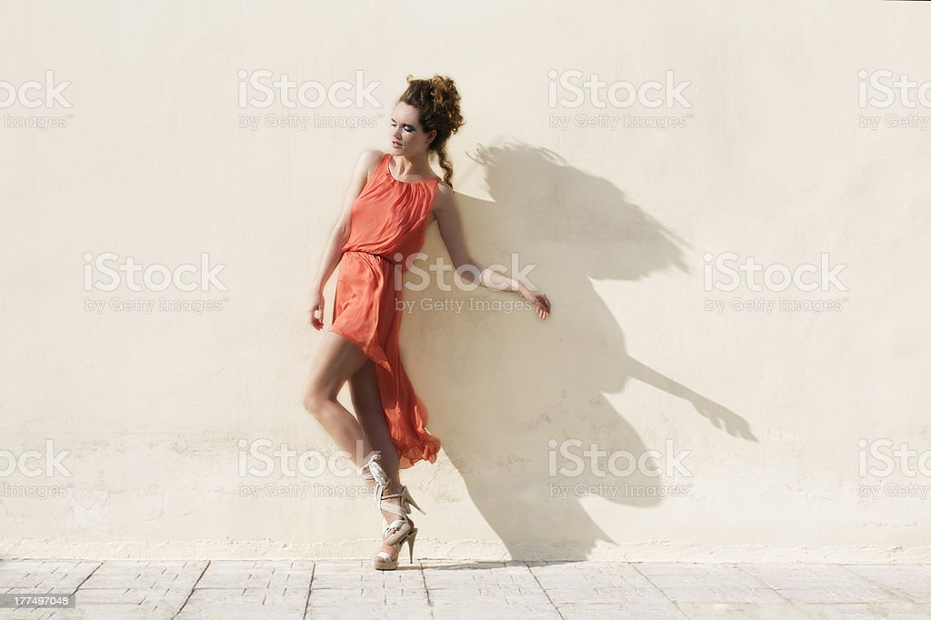 Model in a red dress posing against a white wall stock photo
