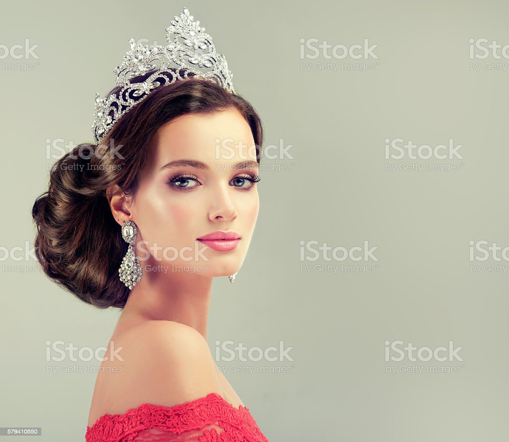 Model in a red gown and crown on her head. stock photo