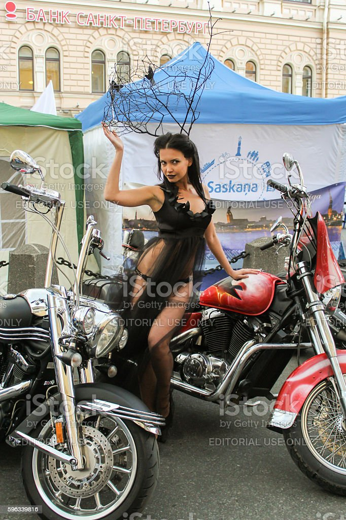 Model in a transparent dress posing in a red motorcycle. Lizenzfreies stock-foto