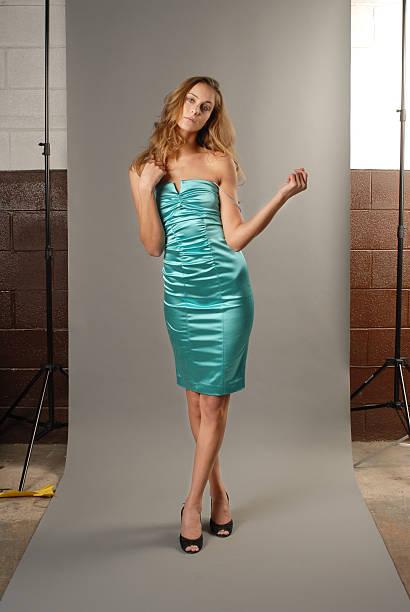 das model im blauen kleid gegen grau papier - türkise haare stock-fotos und bilder