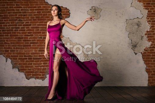 Model in Elegant Dress, Woman Posing in Flying Silk Cloth Waving on Wind, Beauty Fashion Portrait Near Old Brickwork