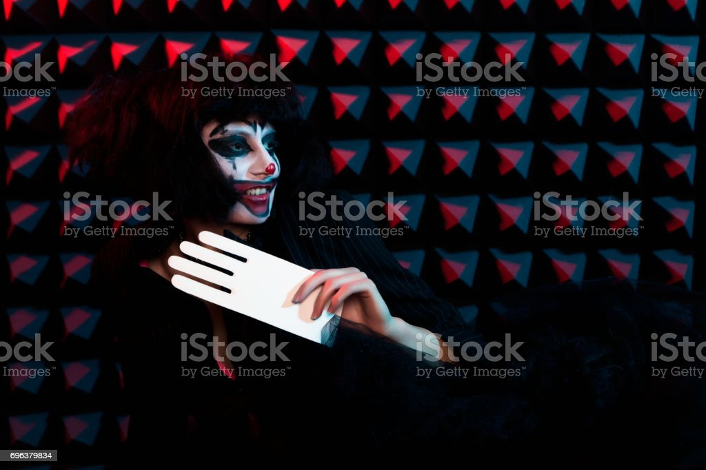 model in makeup of clown with white hand stock photo
