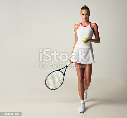 White, elegant tennis outfit on the beautifully looking, tanned woman. Gorgeous young model is holding tennis racket and ball in the hands and makes step forward. Attractiveness of  tennis. Sport, tennis, beauty and fashion.