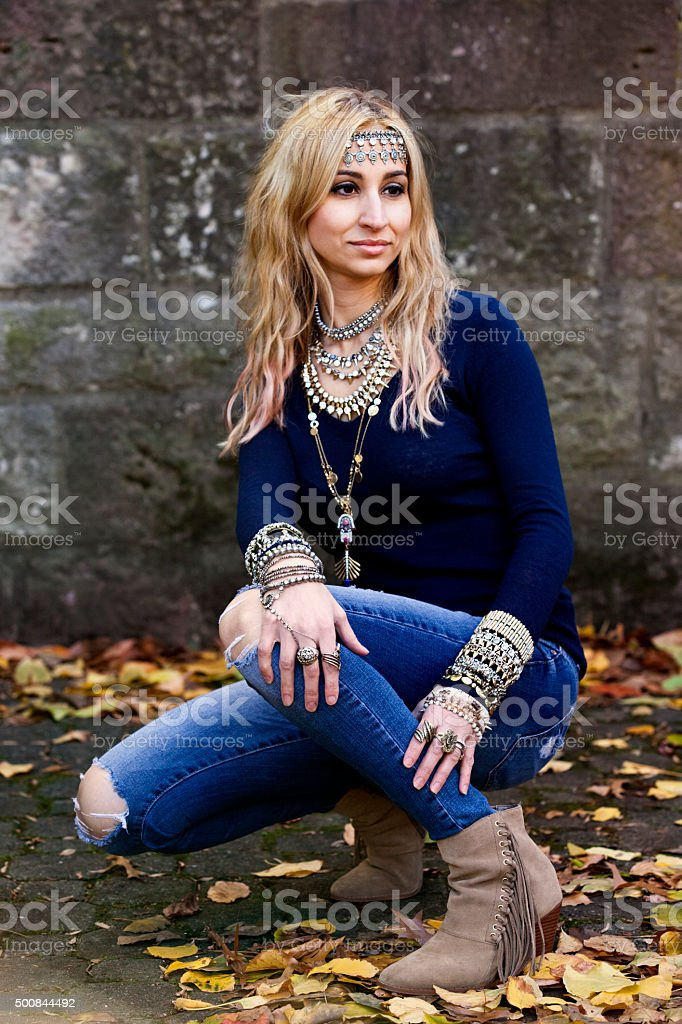 Model kneeling outdoors, torn jeans, Swede  boots, excessive  jewelry stock photo