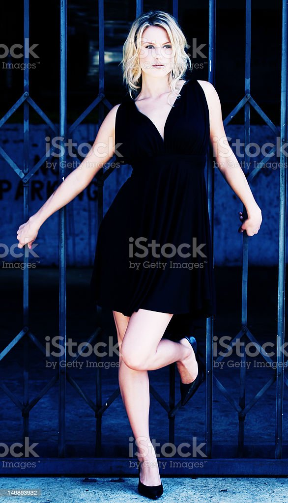 Model leaning on a metal gate royalty-free stock photo