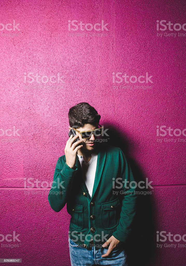 Model man talking with a smart phone over fuchsia background stock photo