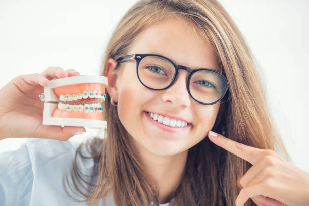 Model of a dental braces in the hand of a young girl with aligned teeth after the process of using a dental brace. stock photo