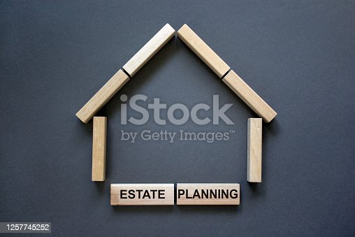 Model of a wooden house from wooden blocks. Words 'estate planning'. Copy space. Business concept. Beautiful grey background.