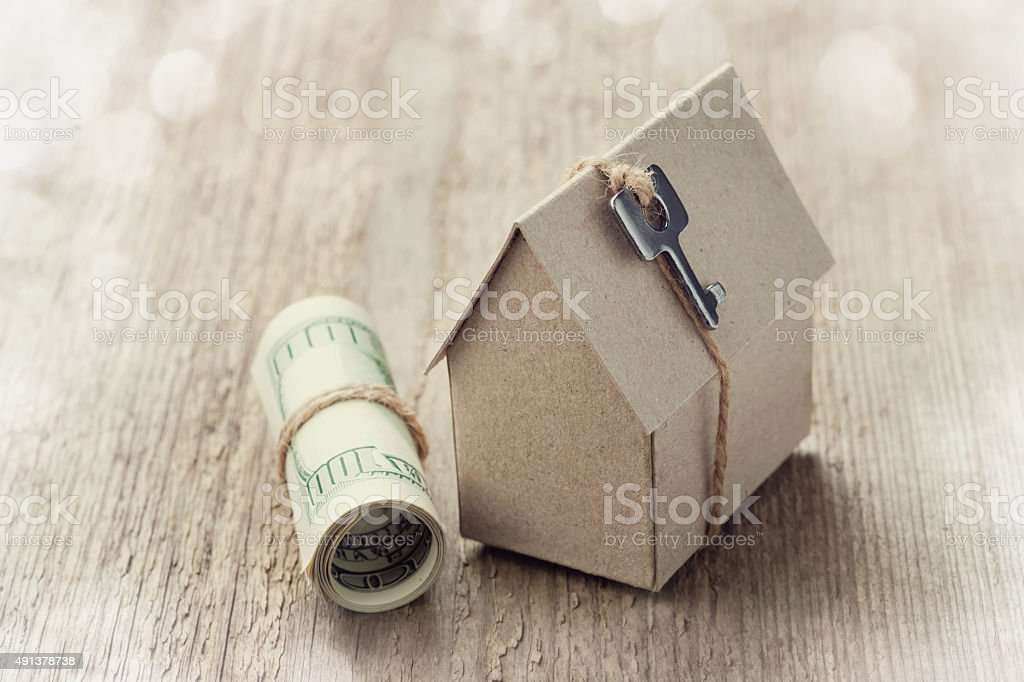 Model of cardboard house with key and dollar bills stock photo