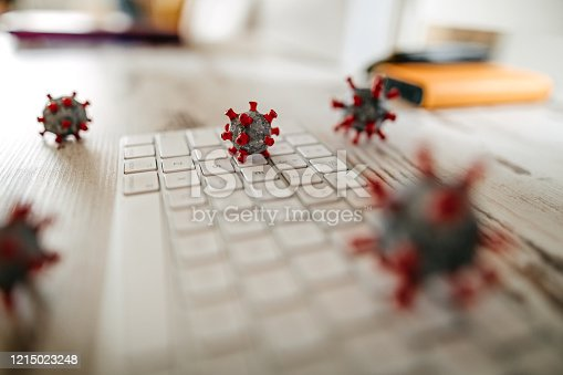 Close up model of corona virus on desk and keyboard in office