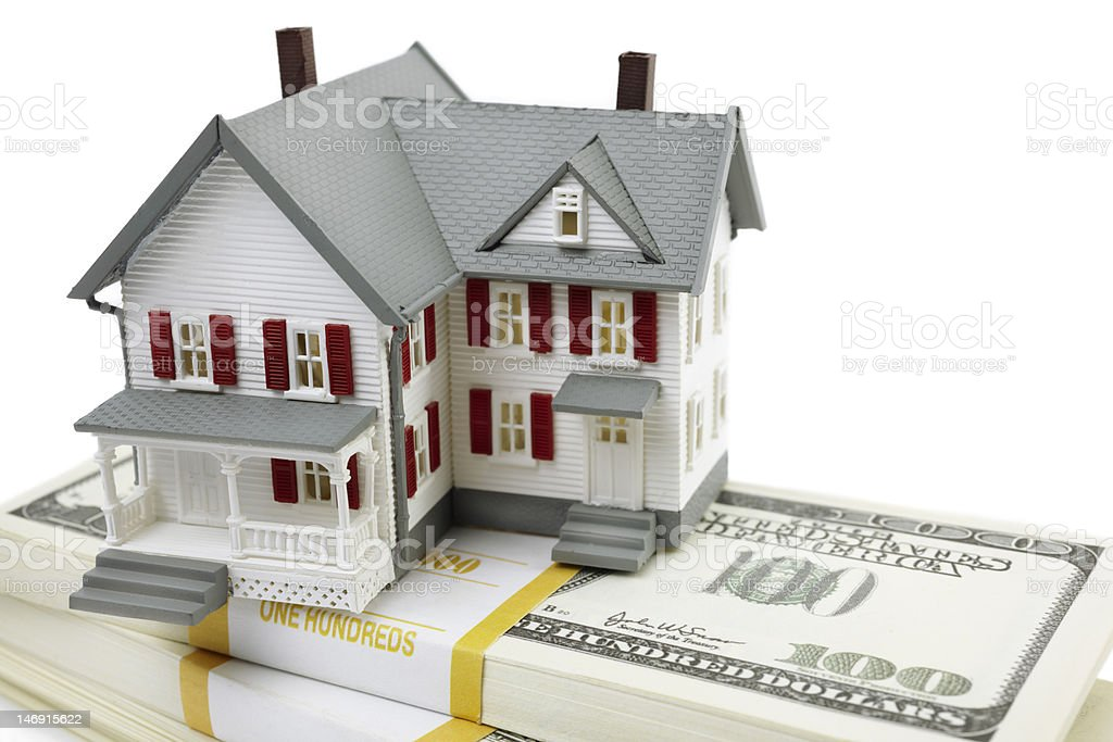 Model of home sitting atop a stack of 100 dollar bills stock photo