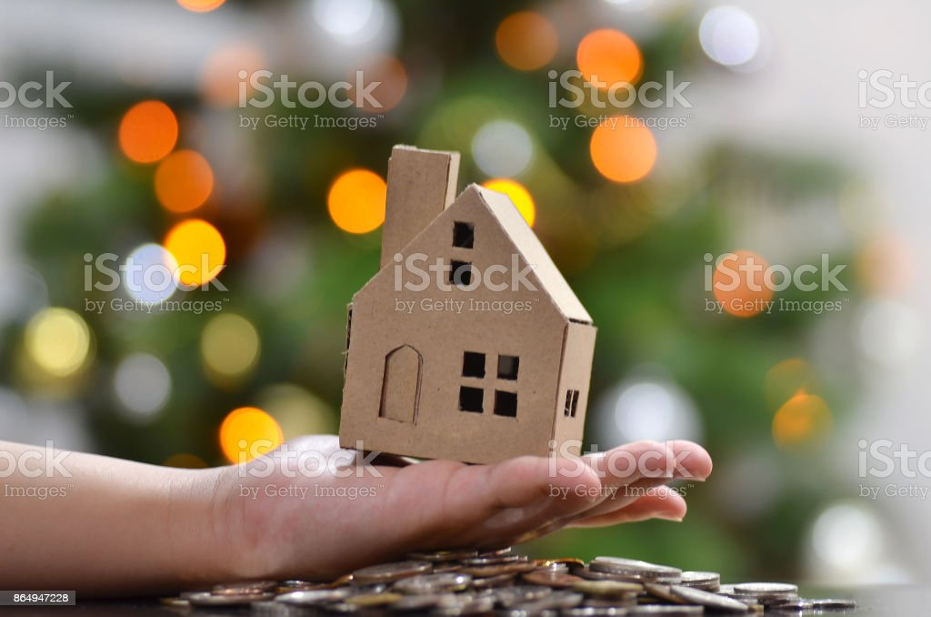 Model of house with coins on wooden table stock photo