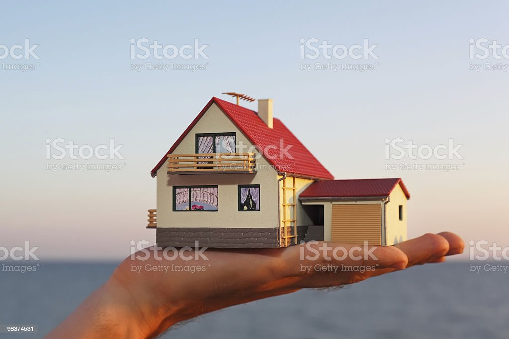 Model of house with garage on hand against sea royalty-free stock photo