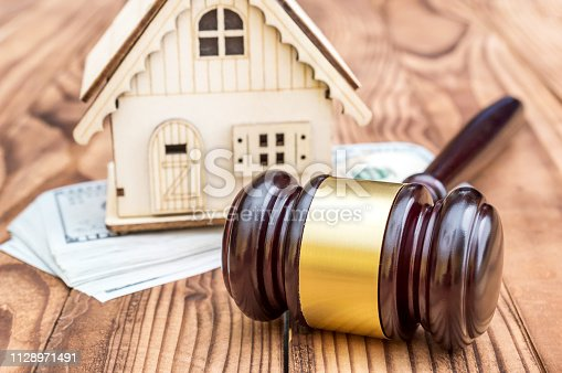 182148217istockphoto Model of house with gavel and money on the table. 1128971491