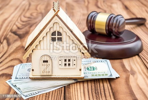 istock Model of house with gavel and money on the table. 1138231670