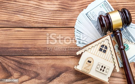 182148217istockphoto Model of house with gavel and money on the table. Top view. Space for text. 1130544960