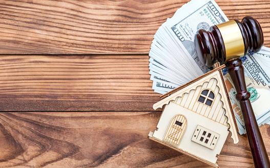 182148217 istock photo Model of house with gavel and money on the table. Top view. Space for text. 1130544960