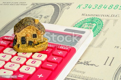 istock Model of the house is on the calculator with dollar background. Real estate loans or save money to buy new house for the family in a future concept. 1145328620
