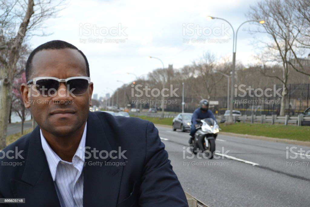 Model on road wearing a business suit and shades; motorcycle stock photo