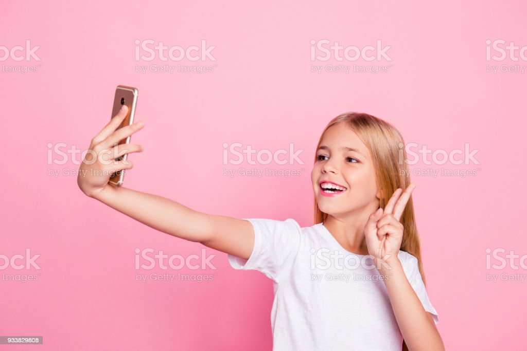Model people education freetime hobby selfie shots pre teen dream concept. Portrait of cute sweet lovely dreamy careless excited cheerful girl taking selfie on telephone isolated on pink background stock photo