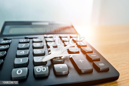 istock Model plane and calculator on wooden table 1058206702