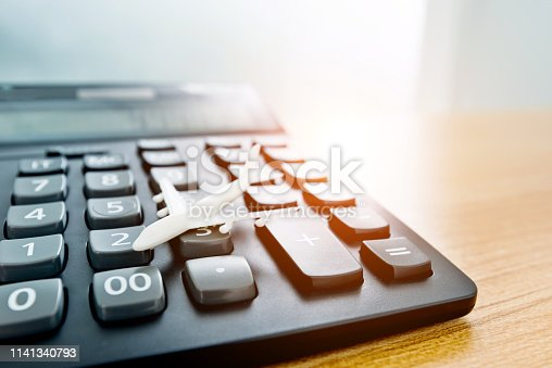 istock Model plane and calculator on wooden table 1141340793