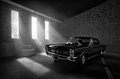 Beaconsfield, UK - July 01, 2019: A scale model of a Pontiac GTO in an old garage setting. The model car is sitting in an atmospherically-lit industrial garage environment. The garage environment/model is made out of fibre-board, and was photographed in my studio in Beaconsfield. There is no one in the photograph.