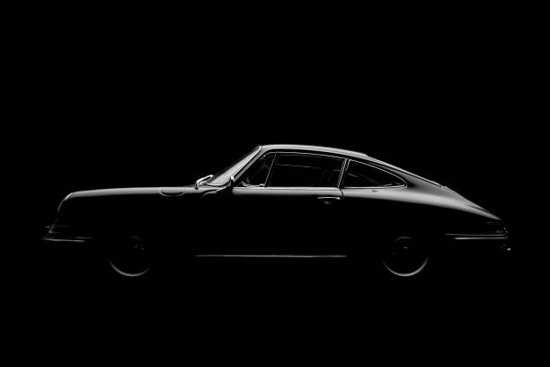 Model Porsche 911 In Black And White Beaconsfield, UK - November 28, 2016: A 1:18 scale model of a 1964 Porsche 911, set against a solid black background. Low key/black & white image. porsche stock pictures, royalty-free photos & images