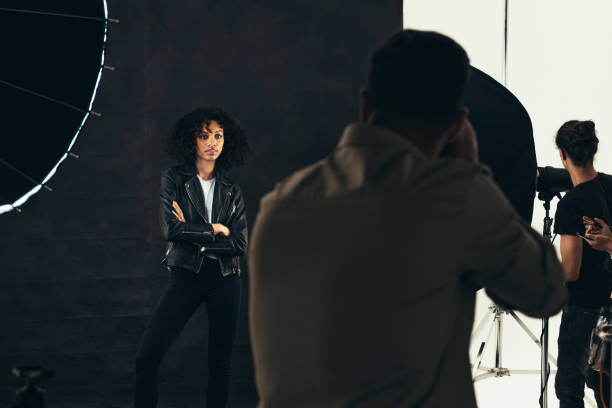 Model posing for a photograph during a photo shoot Rear view of a photographer taking photos of female model. Photographer with his team during a photo shoot. retail equipment stock pictures, royalty-free photos & images