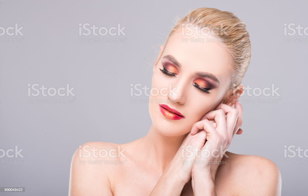 Model posing with eyes closed wearing professional make-up stock photo