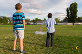 These two boys are launching a model rocket in a large playground field.  This photo shows the moment of ignition as the rocket is pushing off from its platform trailing a flame and smoke.
