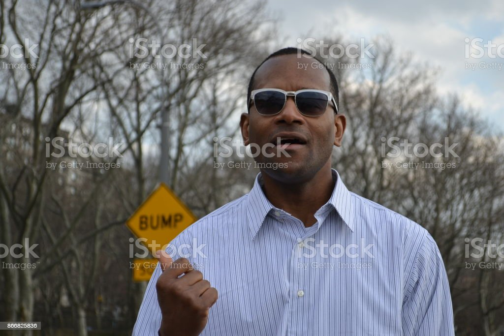 Model singing, wearing a collared dress shirt and shades stock photo