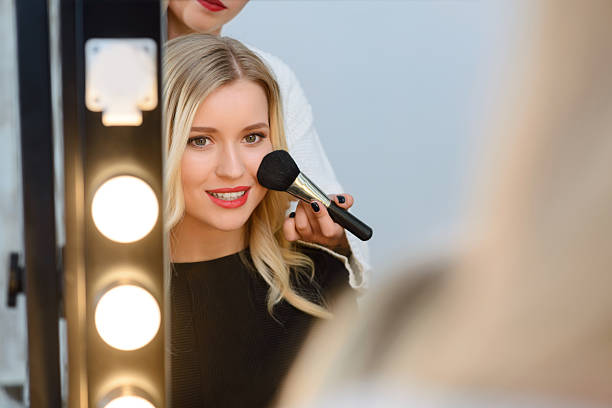 model sitting in front of mirror while applying blush - makeup artist bildbanksfoton och bilder