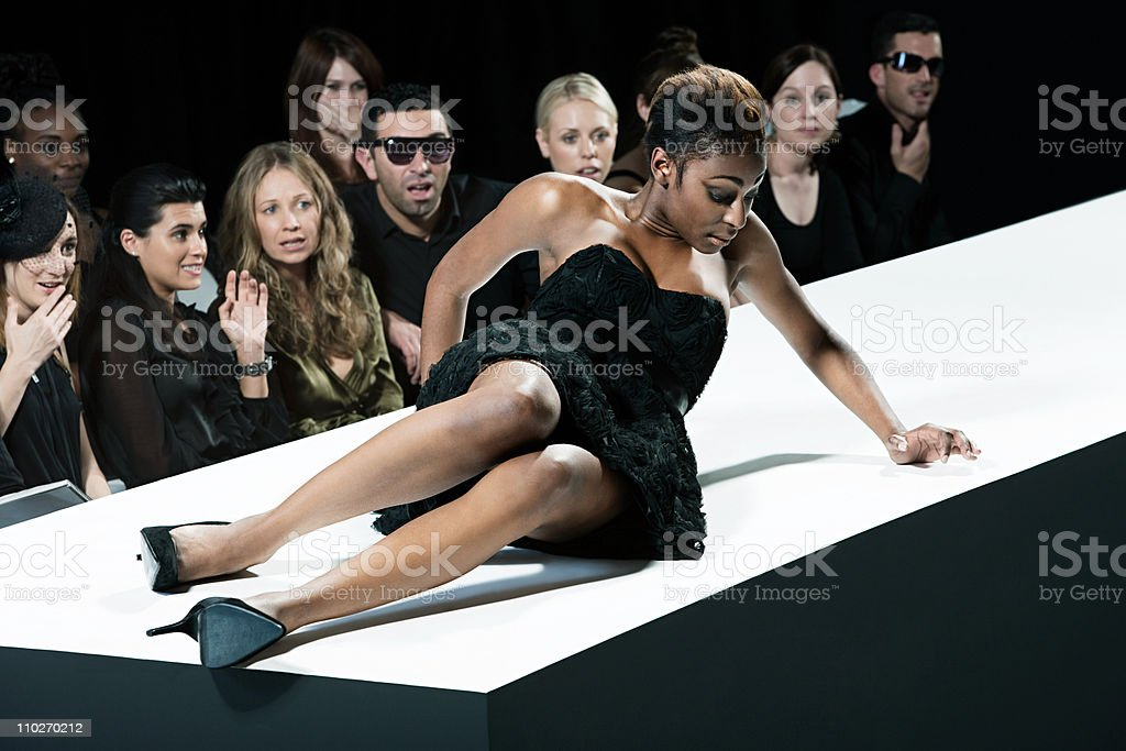 Model sitting on catwalk having fallen down at fashion show stock photo