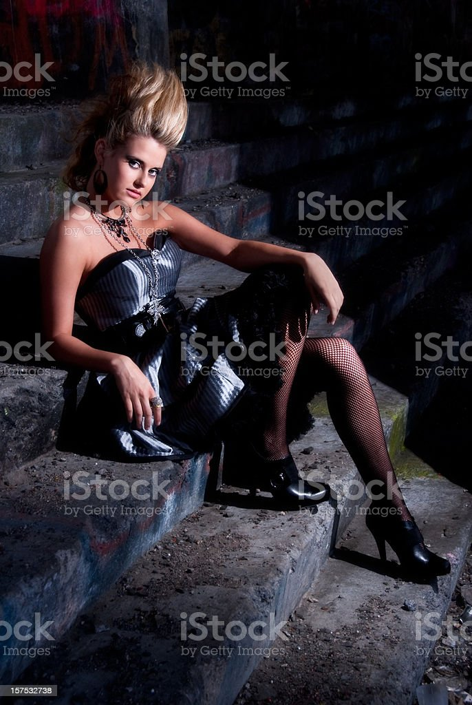 Model sitting on the steps inside abandoned house with graffiti royalty-free stock photo