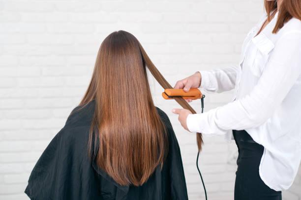model vergadering terwijl hairstyling in beaty salon met witte bakstenen muren. - bijstellen stockfoto's en -beelden