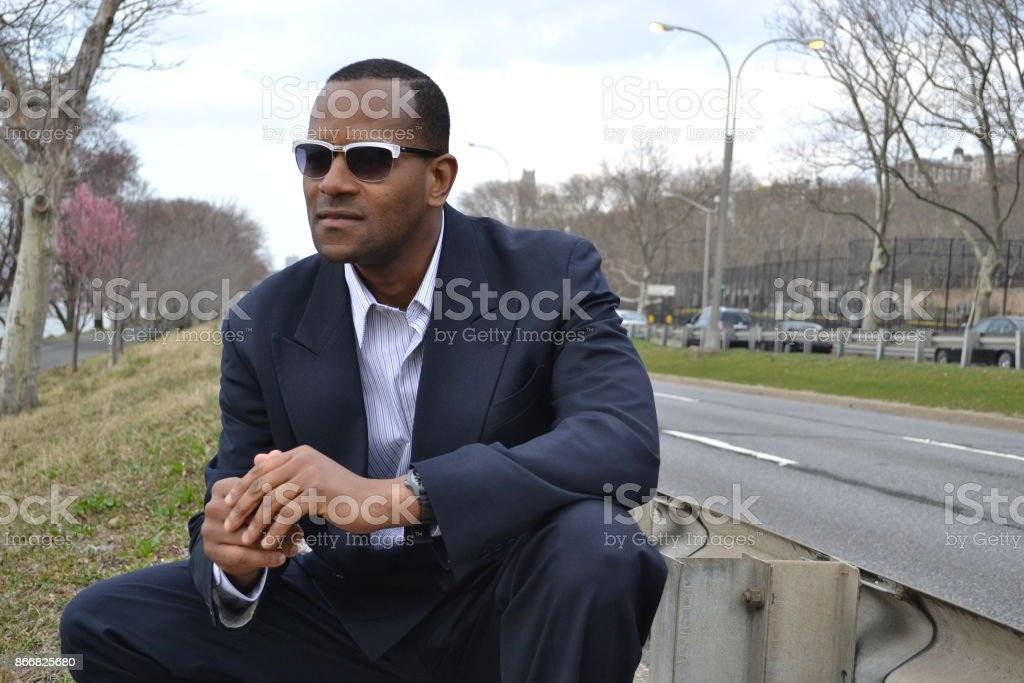 Model smiling and kneeling while wearing a business suit and shades stock photo