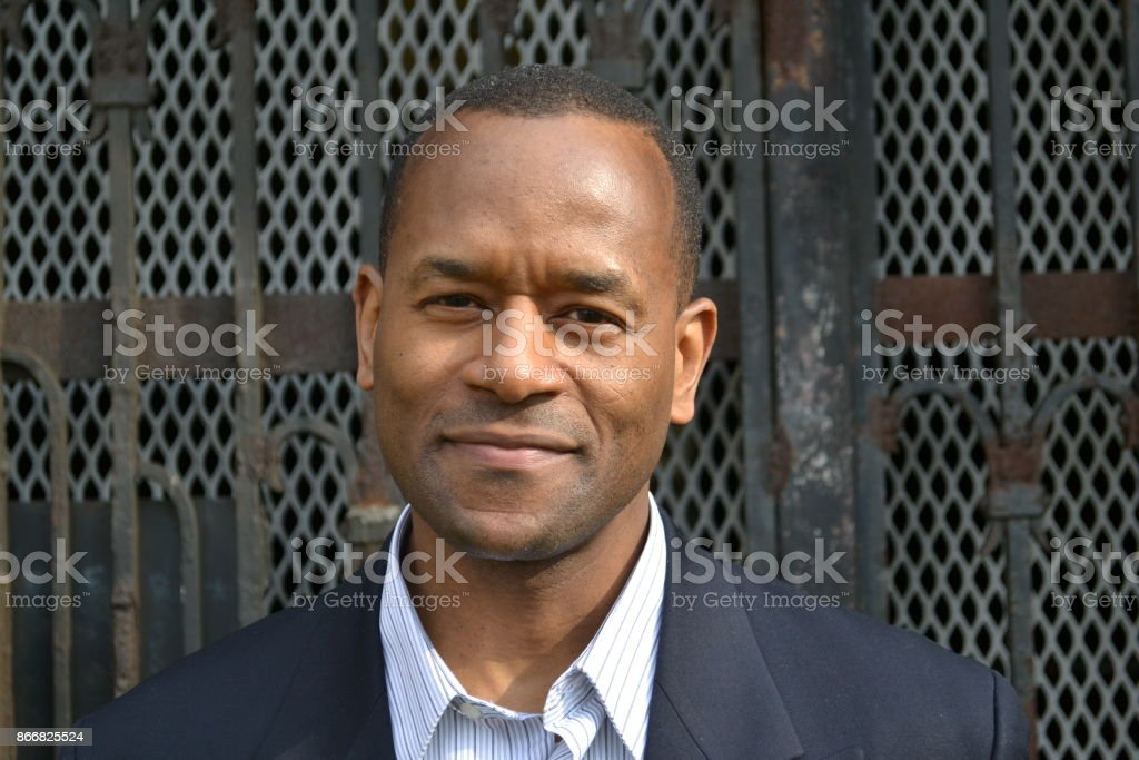 Model smiling wearing a business suit and in front of a gate stock photo