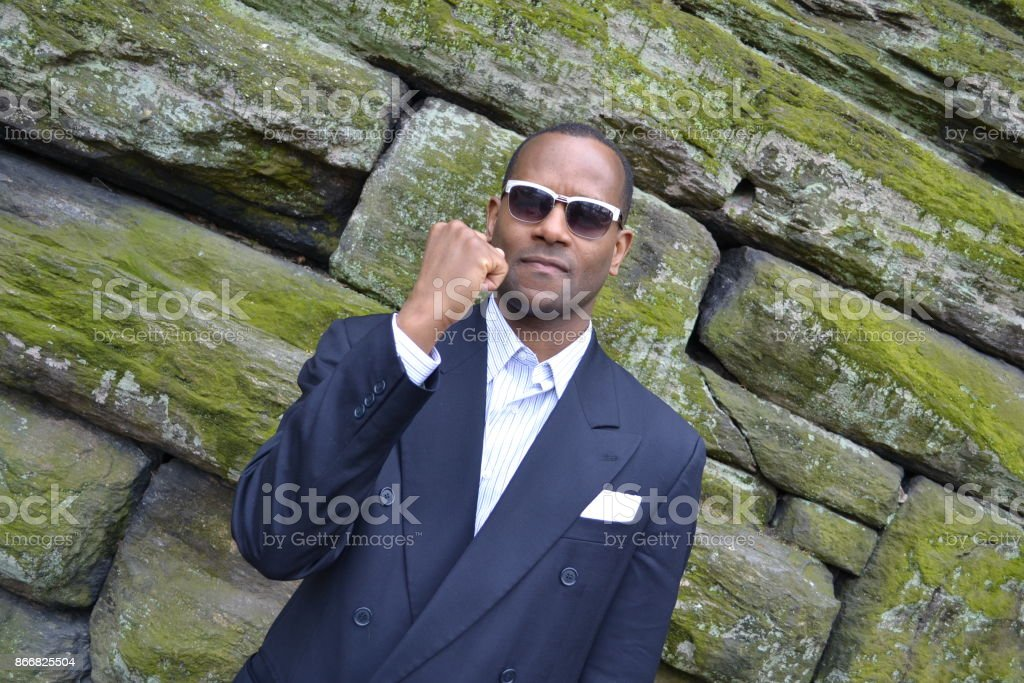 Model smiling wearing a business suit and shades stock photo