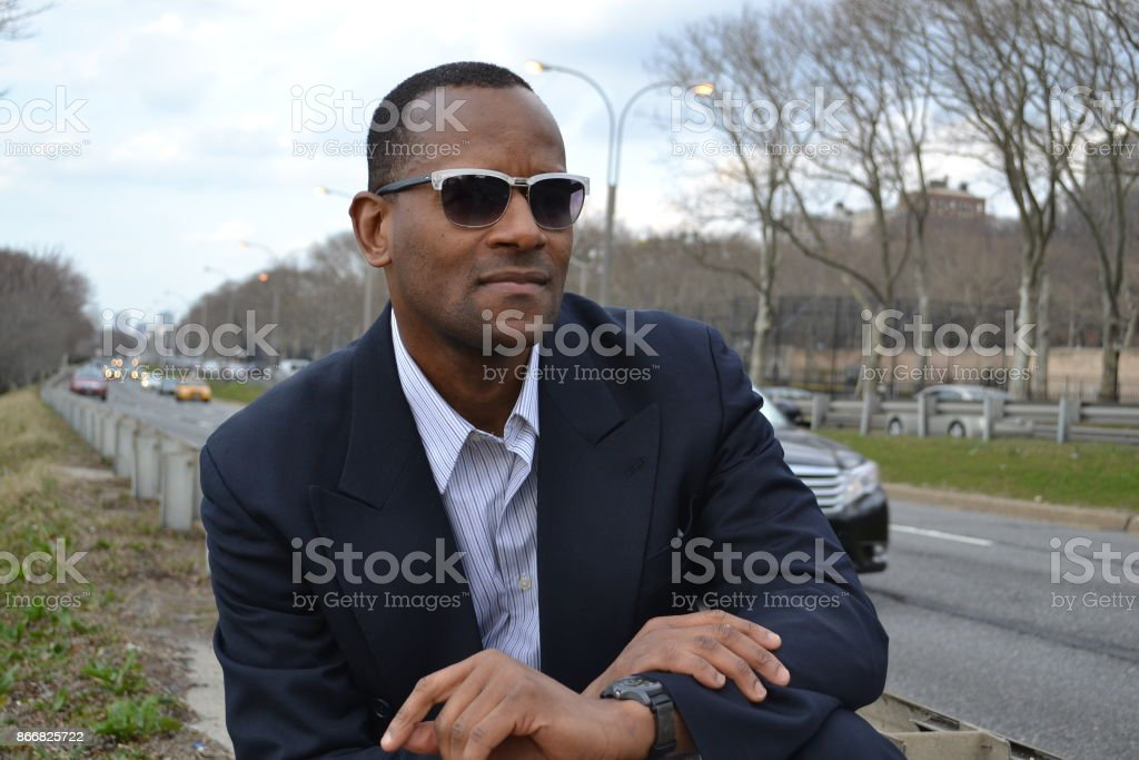 Model smiling wearing a business suit and shades; roadside, Riverside stock photo