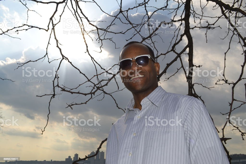 Model smiling, wearing a collared dress shirt and shades stock photo