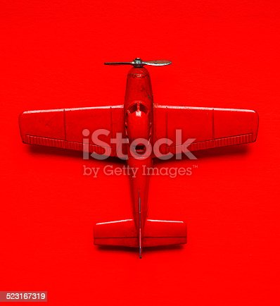 Vintage red airplane model metal toy  over a red background