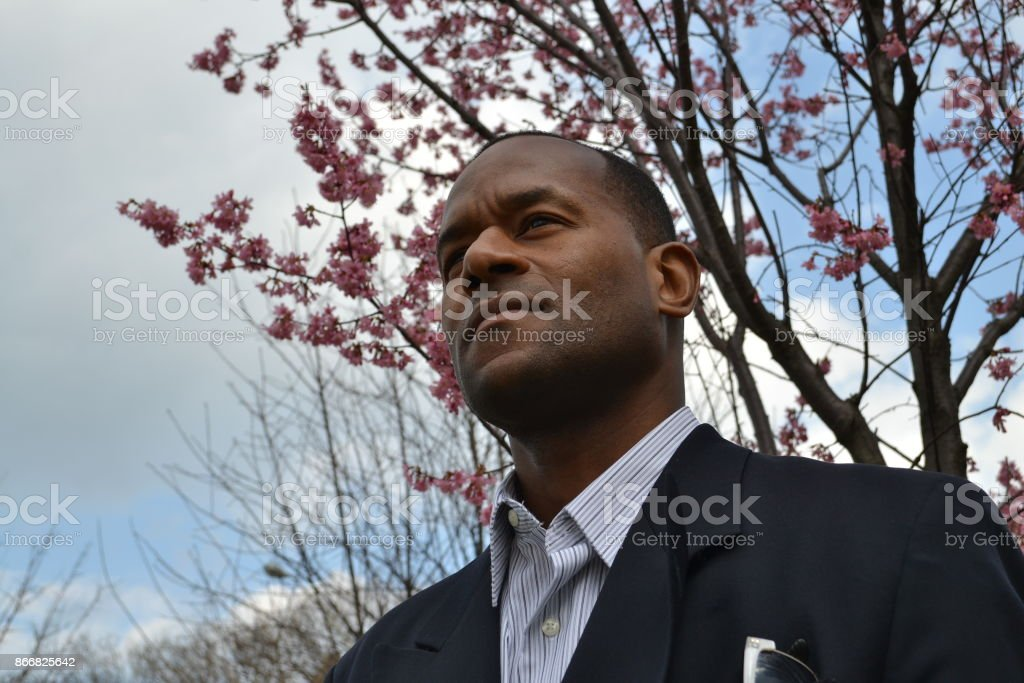 Model wearing a business suit and shades looking ahead stock photo