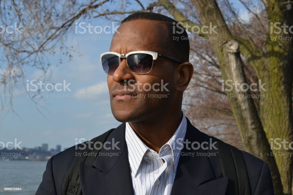 Model wearing a business suit, collared dress shirt and shades stock photo