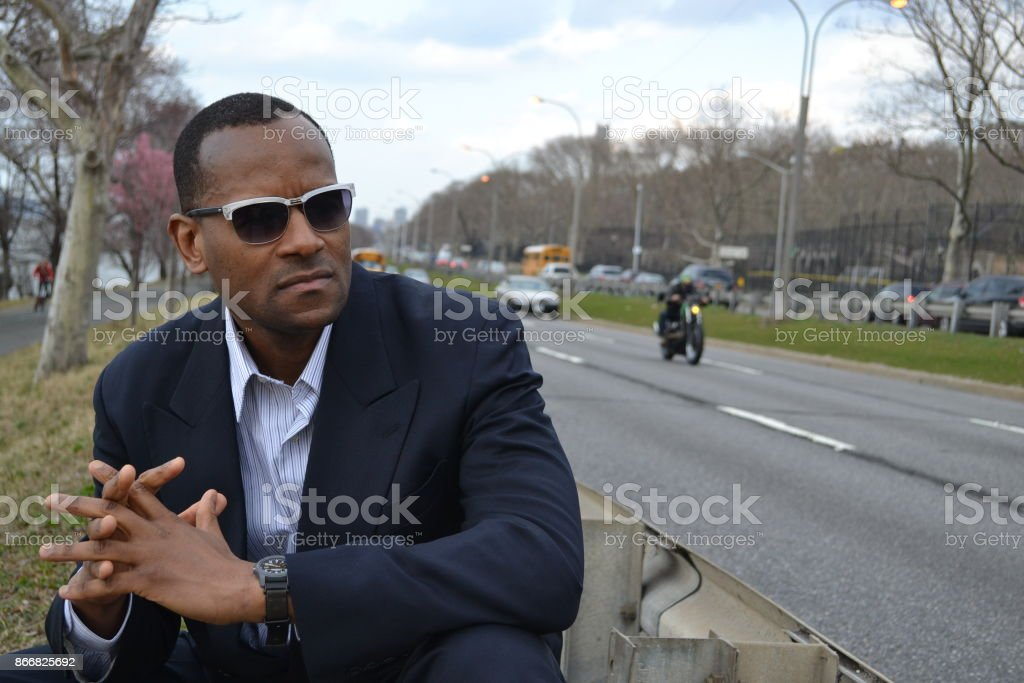 Model wearing a business suit, shades; motorcycle; Riverside Park NYC stock photo